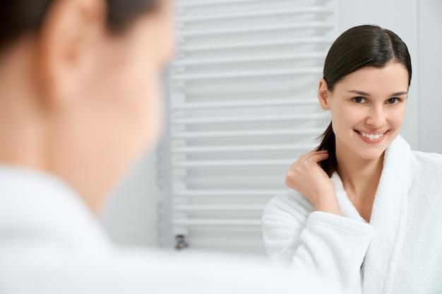 Attraente giovane donna in piedi e guardando allo specchio