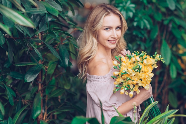 An attractive young woman standing near plants holding delicate yellow freesia in hand