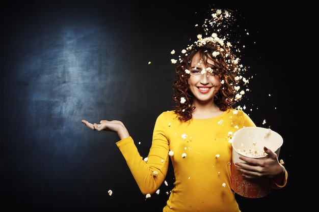Attractive young woman staying under popcorn shower with hand up