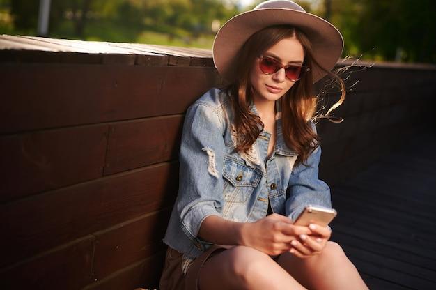 ファッショナブルなサングラスとデニムジャケットの魅力的な若い女性の学生は、木製のテラスに座ってスマートフォンを使用します