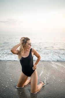 Attractive young woman in sunglasses kneels in the sea at sunset light in a black swimsuit. selective focus