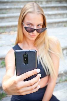 Attractive young woman in sunglasses taking selfie.