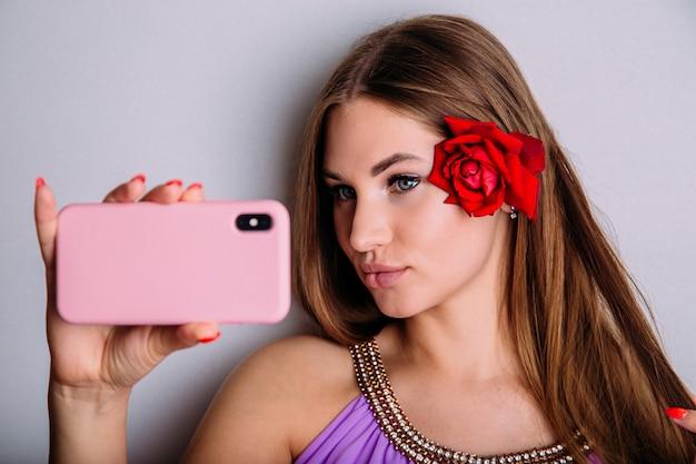 魅力的な若い女性はスマートフォンでselfieを取り、唇をふくれっ面にして、赤いバラの花で髪を整えます。