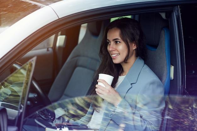 ラップトップノートブックとコーヒーブレイク成功した実業家を取っている魅力的な若い女性