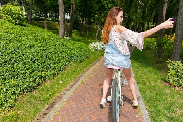 公園で自転車に座ってスマートフォンで写真を撮る魅力的な若い女性