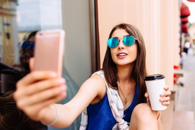 彼女の携帯電話でテイクアウトコーヒーと写真を撮る魅力的な若い女性