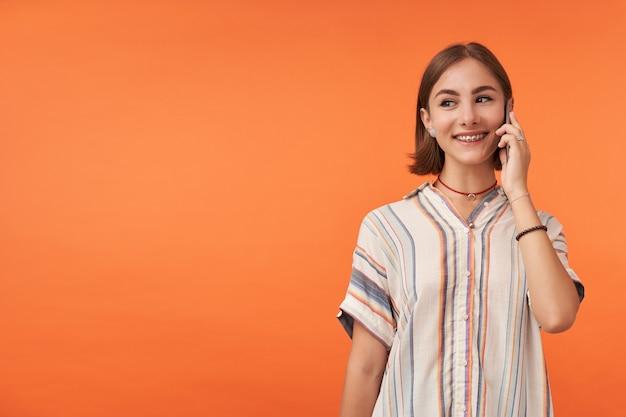 매력적인 젊은여자가 스마트 폰에 얘기 하 고 좋은 이야기를 가지고 오렌지 벽 위에 복사 공간에서 왼쪽을 찾고. 줄무늬 셔츠, 치아 교정기 및 팔찌 착용.