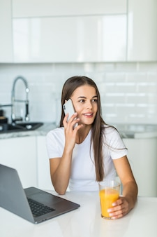 Attractive young woman talking on mobile phone while standing on a kitchen with glass of juice