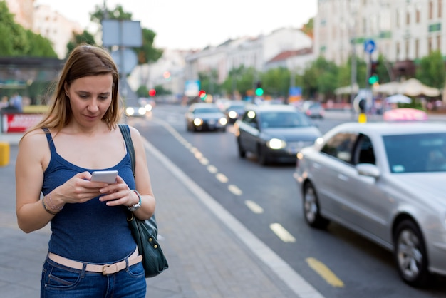 Attractive young woman texting on the street