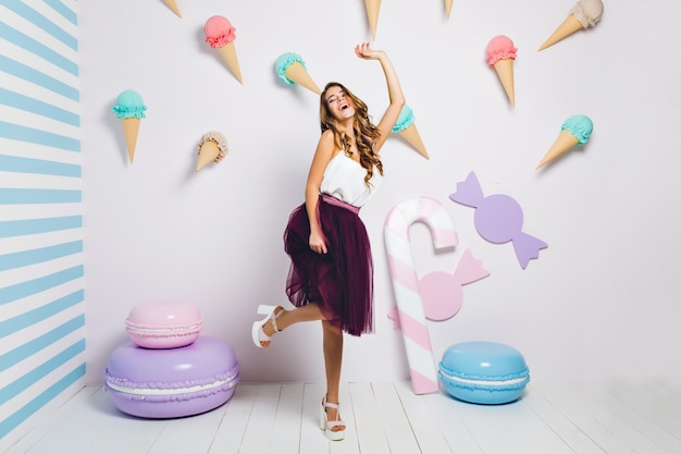 Attractive young woman in trendy white shoes dancing with cheerful smile on theme party. portrait of pretty joyful girl having fun in room with sweet interior decorated with macaroons.