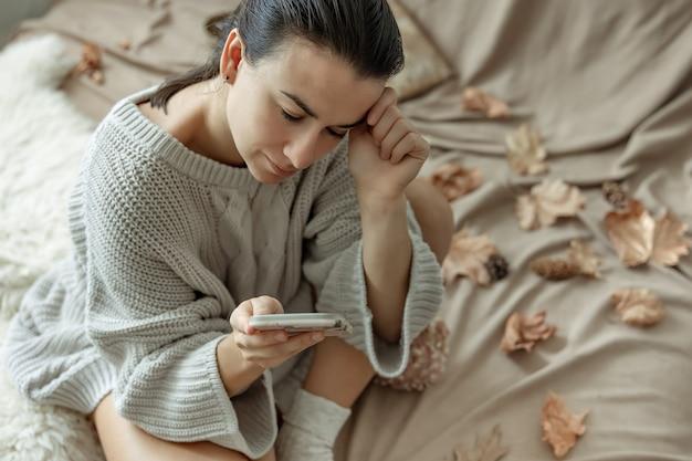 Привлекательная молодая женщина пользуется телефоном, сидя в постели среди осенних листьев в уютном вязаном свитере.