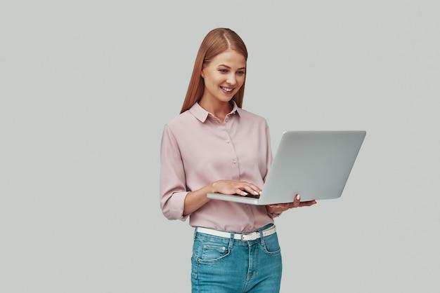 Привлекательная молодая женщина с помощью ноутбука и улыбается, стоя на сером фоне