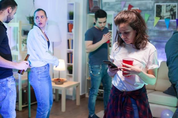 그녀의 친구들이 배경에서 춤을 추는 동안 스마트폰을 사용하는 매력적인 젊은 여성.