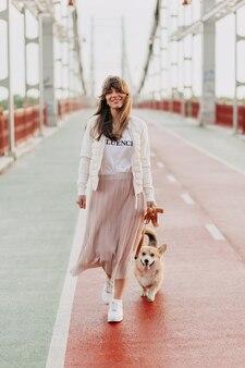 Attraente giovane donna che cammina corgi all'aperto