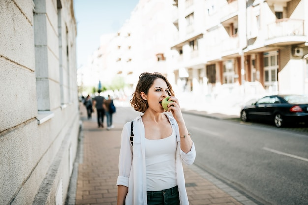 Attractive young woman walking on street and eating apple.