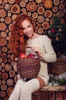 白いウールのセーターとニットの靴下を身に着けている魅力的な若い女性。クリスマス。