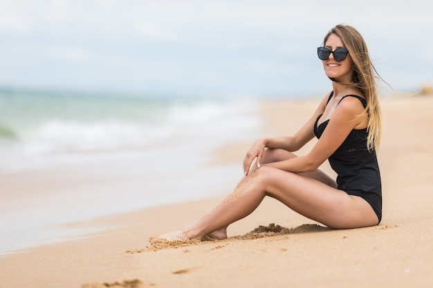 Una giovane donna attraente che indossa un bikini nero si siede su una spiaggia con il gomito sul ginocchio