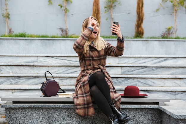 Attractive young woman wearing coat sitting outdoors, taking a selfie