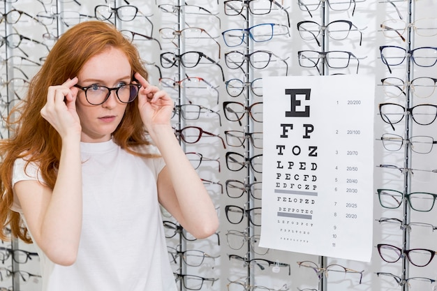 Attractive young woman wearing eyeglasses standing neat snellen chart in optica