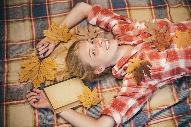 秋の気分でおしゃれな季節の服を着ている魅力的な若い女性。