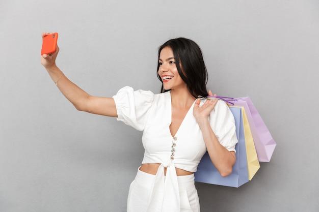 灰色の壁の上に孤立して立っている夏の服を着て、自分撮りを取り、買い物袋を運ぶ魅力的な若い女性