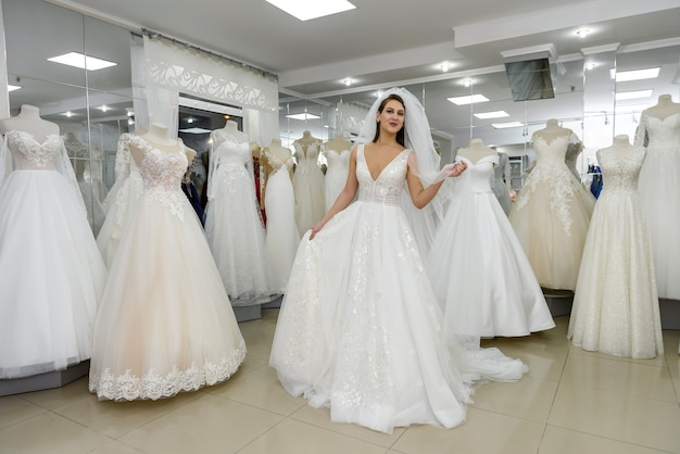 Attractive young woman wearing wedding dress in bridal shop