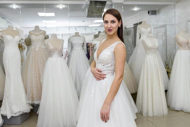 ブライダルショップでウェディングドレスを着ている魅力的な若い女性
