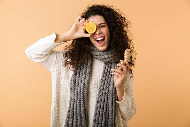 白い壁に孤立して立っている間生姜とレモンを示す冬のスカーフを身に着けている魅力的な若い女性