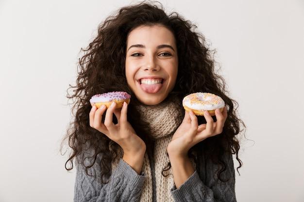 白い壁の上に孤立して立っている間甘いドーナツを示す冬のスカーフを身に着けている魅力的な若い女性