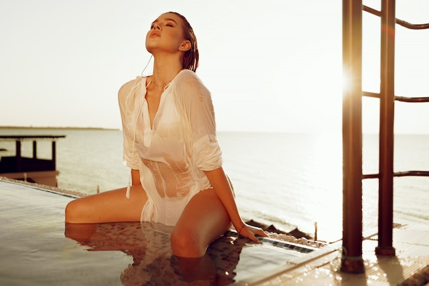 Attractive young woman in wet white shirt in a pool