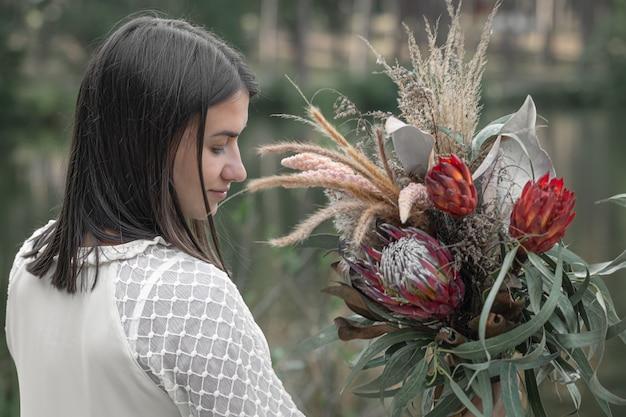 エキゾチックなプロテアの花の花束を持つ魅力的な若い女性。