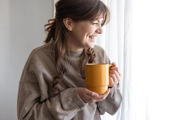 창가에 뜨거운 음료 한 잔을 들고 있는 매력적인 젊은 여성