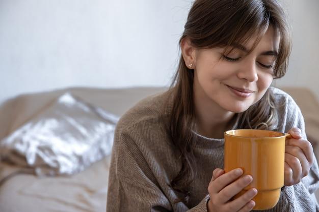 흐릿한 배경에 뜨거운 음료 한 잔을 들고 있는 매력적인 젊은 여성