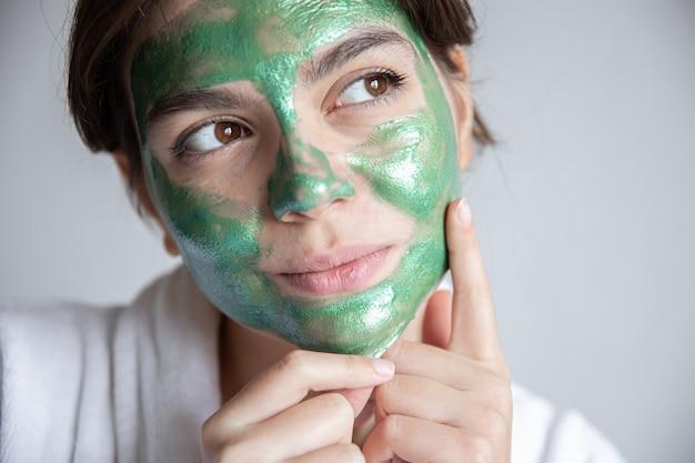 彼女の顔に緑の化粧マスクを持つ魅力的な若い女性
