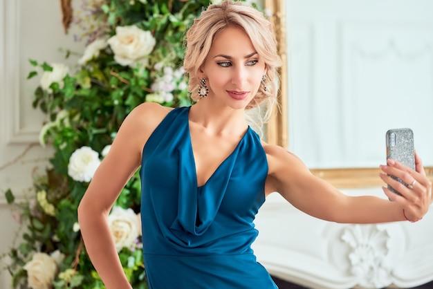 エレガントなドレスでスタイリッシュな髪型を持つ魅力的な若い女性は、自分撮りポーズを作ります