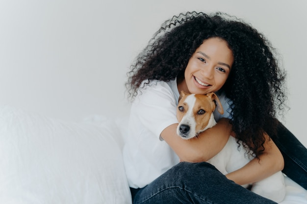 Attractive young woman with afro hircut, embraces with love dog, takes care of pet, smiles gently, wears casual clothing