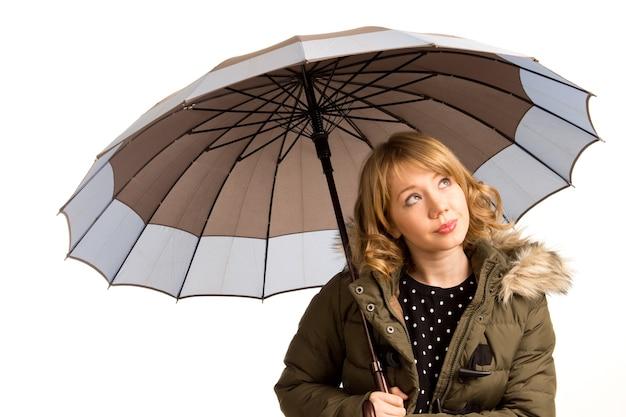 空を見上げる傘を持つ魅力的な若い女性は、白で隔離の雨の天気を見て