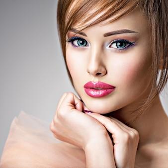 아름 다운 큰 파란 눈을 가진 매력적인 젊은 여자. 섹시한 입술을 가진 놀라운 여자의 근접 촬영 얼굴.