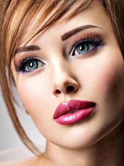 美しい大きな青い目をした魅力的な若い女性。セクシーな唇を持つ素晴らしい女の子のクローズアップの顔。