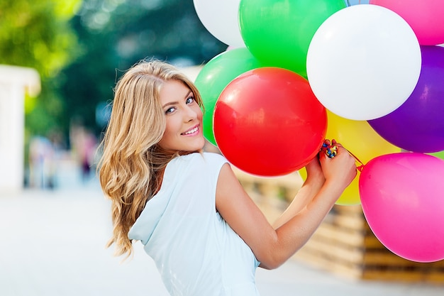 誕生日の風船と赤いギフトボックスを持つ魅力的な若い女性