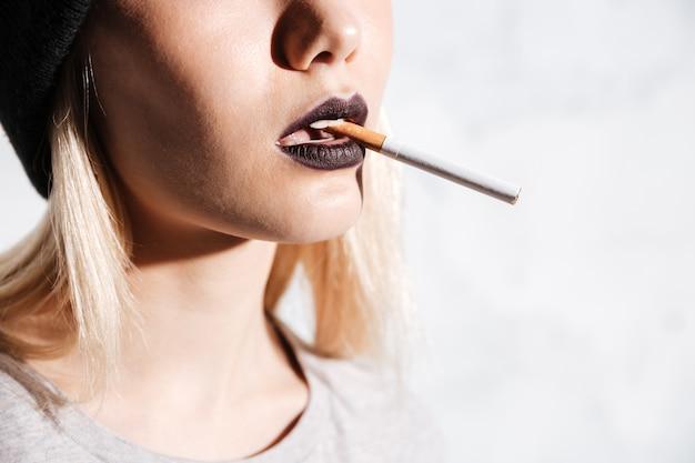 Привлекательная молодая женщина с черной помадой курит сигарету на белом фоне