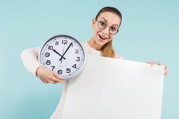 空白のプラカードと時計を持つ魅力的な若い女性