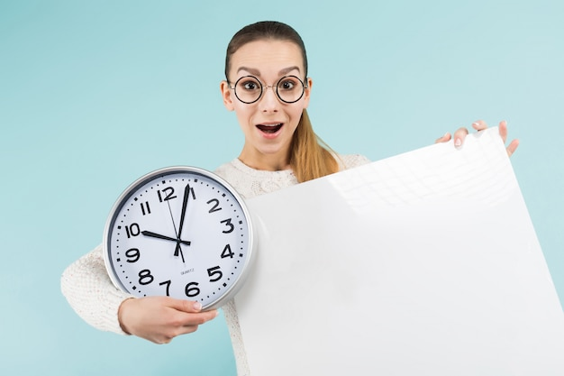 Attractive young woman with blank placard and clock
