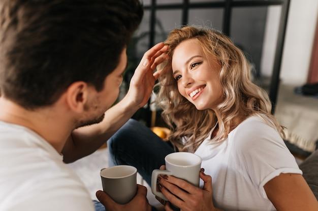그녀의 남자 친구를보고 그는 그녀의 머리를 고정하는 동안 웃 고 금발 머리를 가진 매력적인 젊은 여자. 집에서 함께 시간을 보내고 사랑에 행복 한 커플.