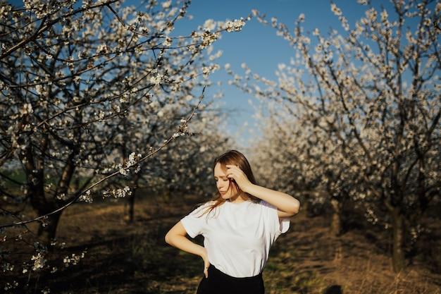 屋外でポーズをとるブロンドの髪を持つ魅力的な若い女性。