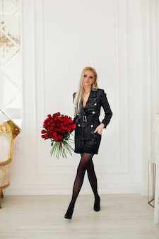 Attractive young woman with blonde hair in stylish black dress hold a bouquet of red roses in luxurious apartments