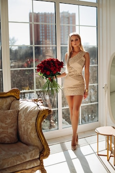 Attractive young woman with blonde hair in stylish dress in luxurious apartment