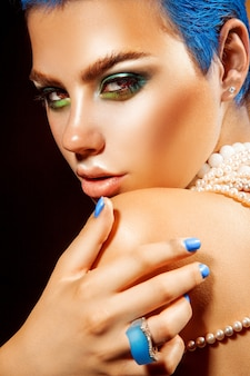 カメラを見て青い爪を持つ魅力的な若い女性