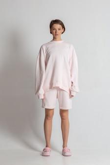白いサイクロラマのピンクのカジュアルな服装でポーズをとるボブの髪型を持つ魅力的な若い女性