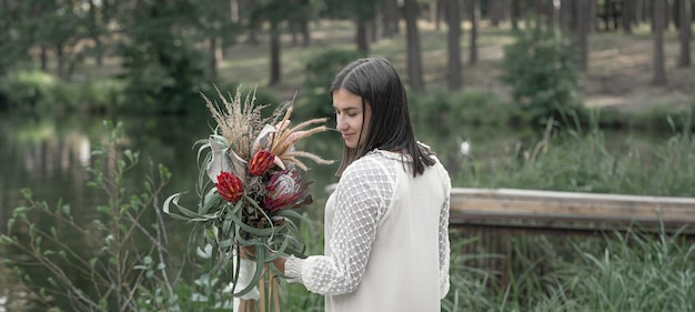 Attraente giovane donna con un mazzo di fiori nella foresta in riva al fiume